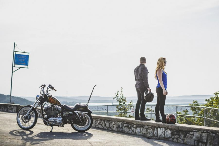 Man and women standing at a scenic overlook in Branson next to their motorcycle.