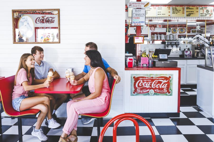 Family of four enjoying an ice cream cone at an old-time ice cream parlor in Downtown Branson.