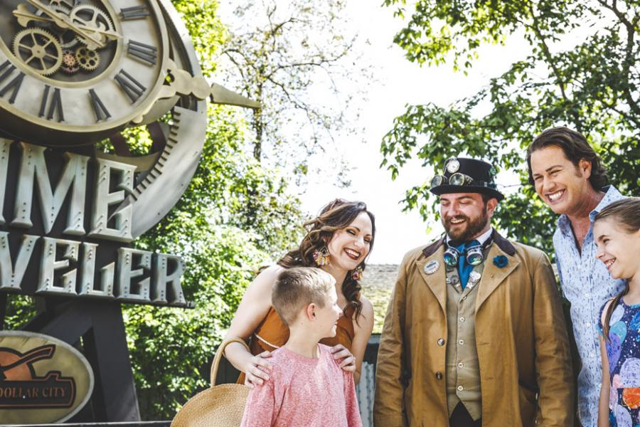 Family of four standing in front of Time Traveler roller coaster with Silver Dollar City staff member.