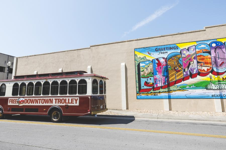 Free Downtown trolley driving in front of a Branson mural.