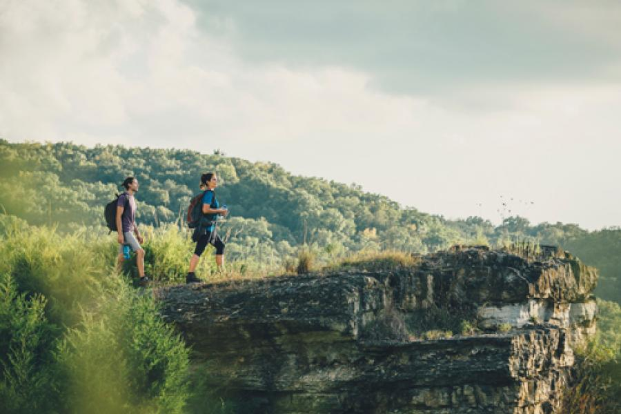 Man and woman standing of the edge of a rock ledge during a scenic hike in Branson.