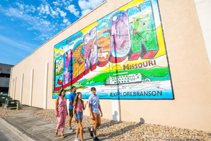 Family of four walking in front of color Downtown Branson mural.