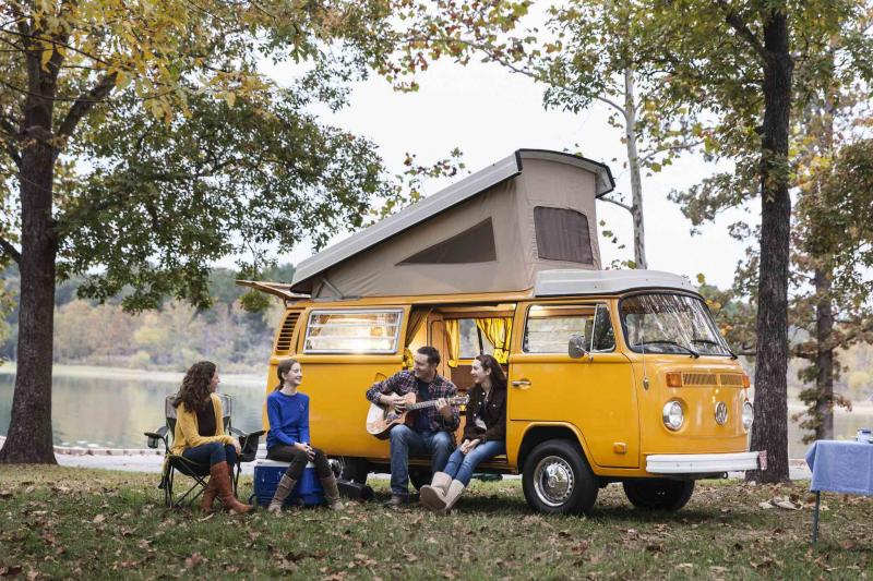 A family sits outside, lakeside next to their Volkswagen pop-top camper van and dad plays the guitar.