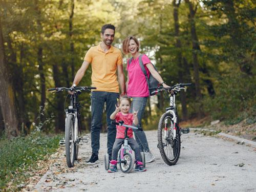Family of three biking on a nature trail in Branson. Young daughter with pigtails is throwing up peace signs with her hands and is the main focus.
