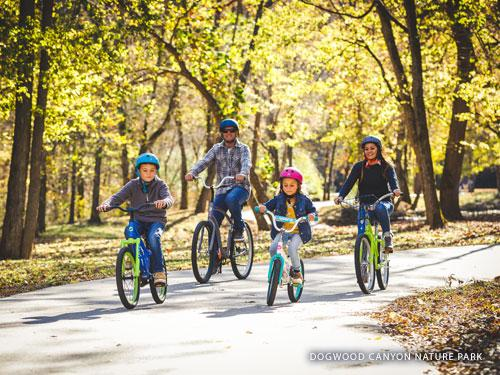 Family of four riding bikes at nature park in Branson.