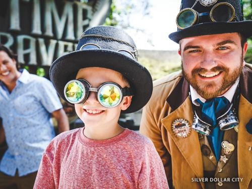 Young boy wearing funny goggles and talking to a theme park worker wearing a vintage costume in Branson.