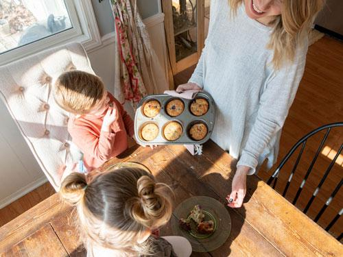 Mom serving her son and daughter homemade blueberry muffins inside a home in Branson.