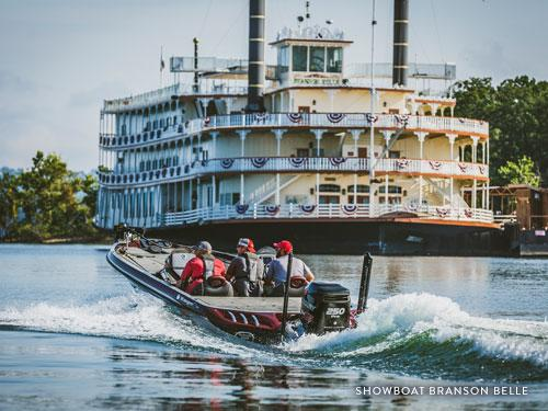 Three men on fishing boats driving beside large Showboat Branson Belle boat on Table Rock Lake in Branson.