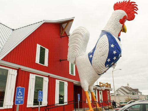 Oversized patriotic chicken in front of a red barn style chicken and steakhouse restaurant on the Branson Strip.