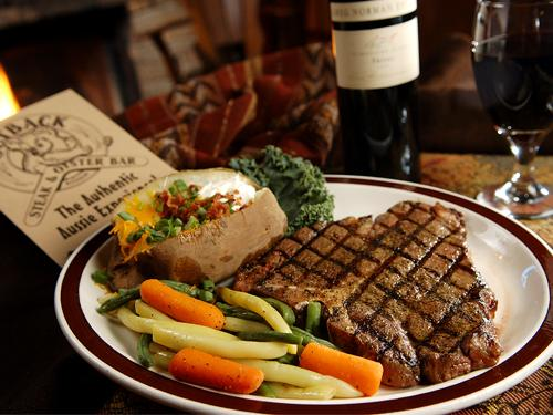 A plate of cooked vegetables, a loaded baked potato and a steak served with wine and an outback steakhouse menu.