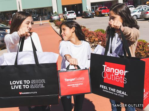 Three sisters holding shopping bags from Tanger Outlets in Branson.