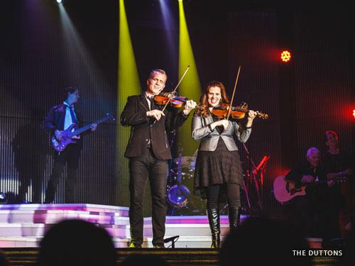 Brother and sister playing violins and singing on Branson stage.