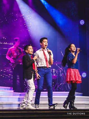 Three young performers singing on a Branson stage.