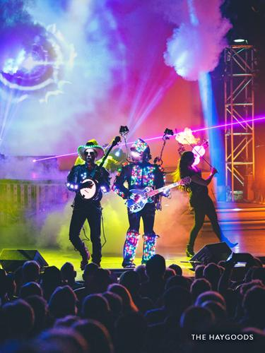 Three performers with lighted costumes and instruments on a live show stage in Branson.