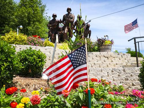 American flag in the foreground and statue of american soldiers in the background. The statue is surrounded by stunning flower displays in an outdoor garden.
