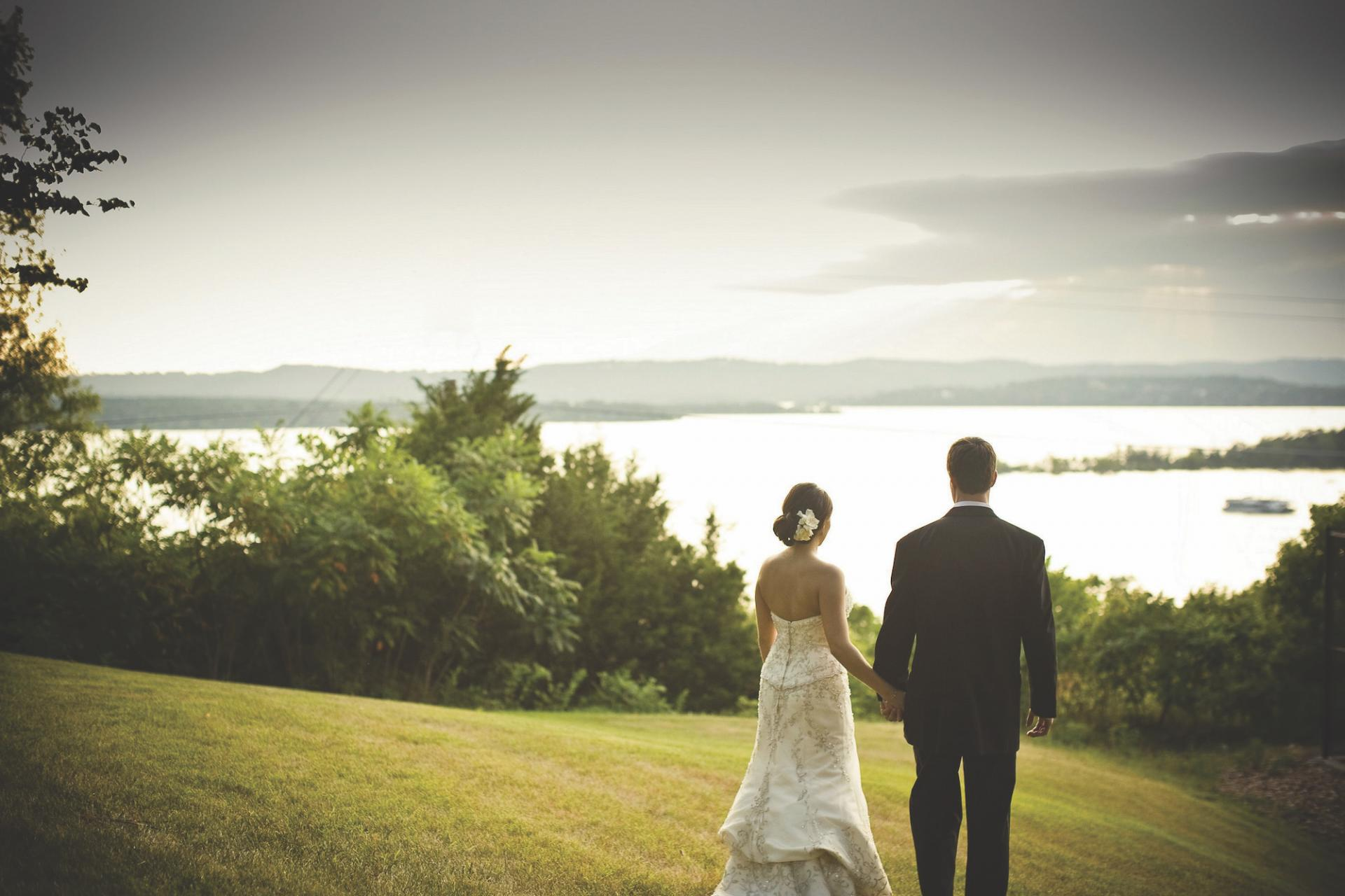 Bride and groom looking into the distant scenery of a lake and rolling hills at Chateau on the Lake Resort.