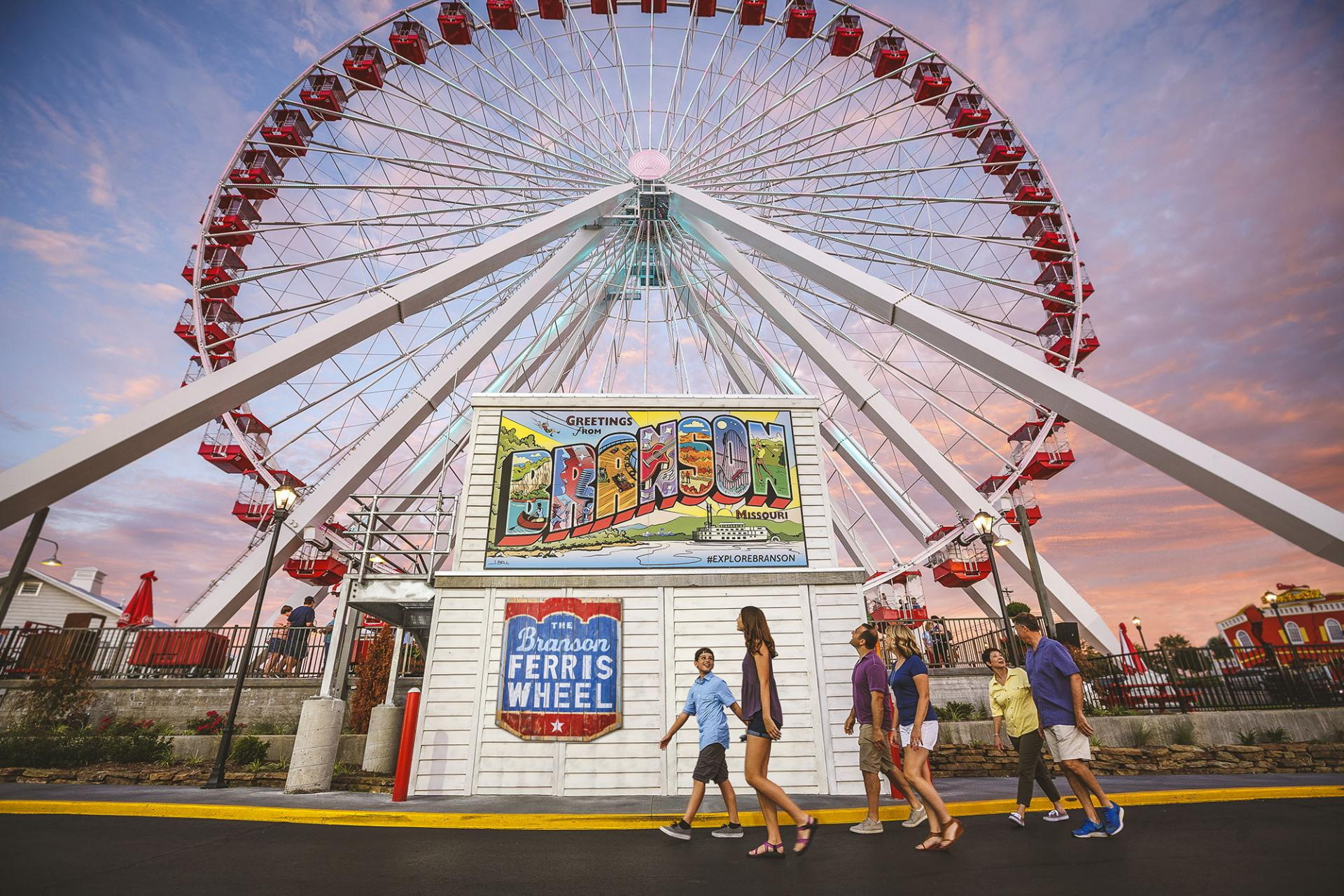 Family walks past a large ferris wheel and Branson mural at dusk.
