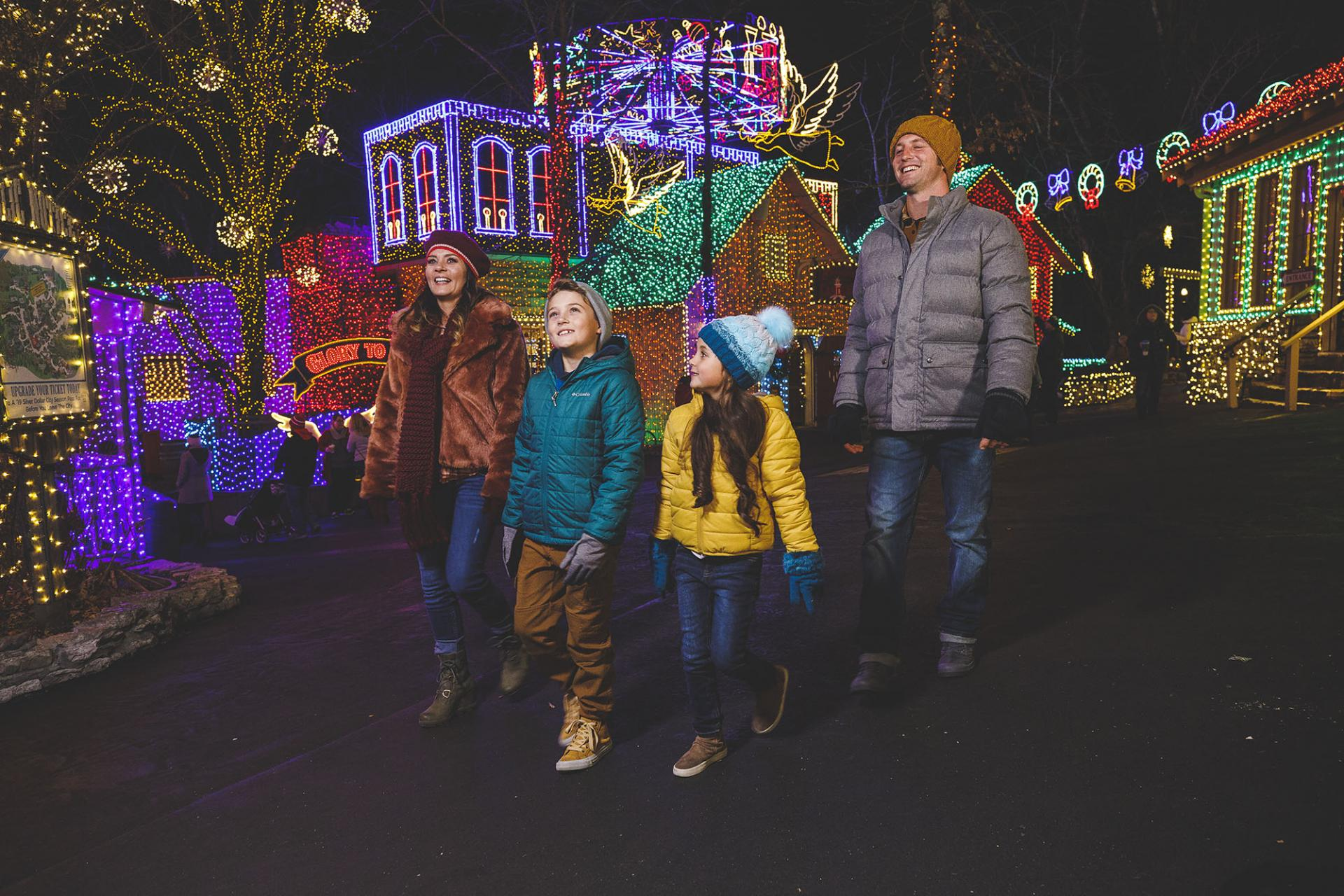 Young family walking through large Christmas light display at Silver Dollar City