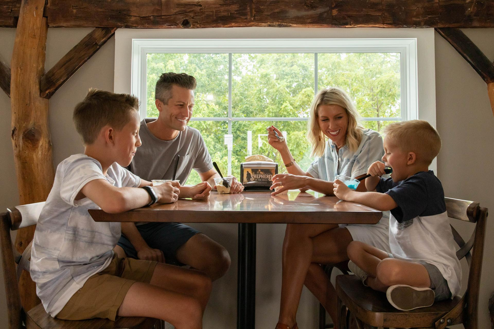 Young family of four enjoying ice cream at a table