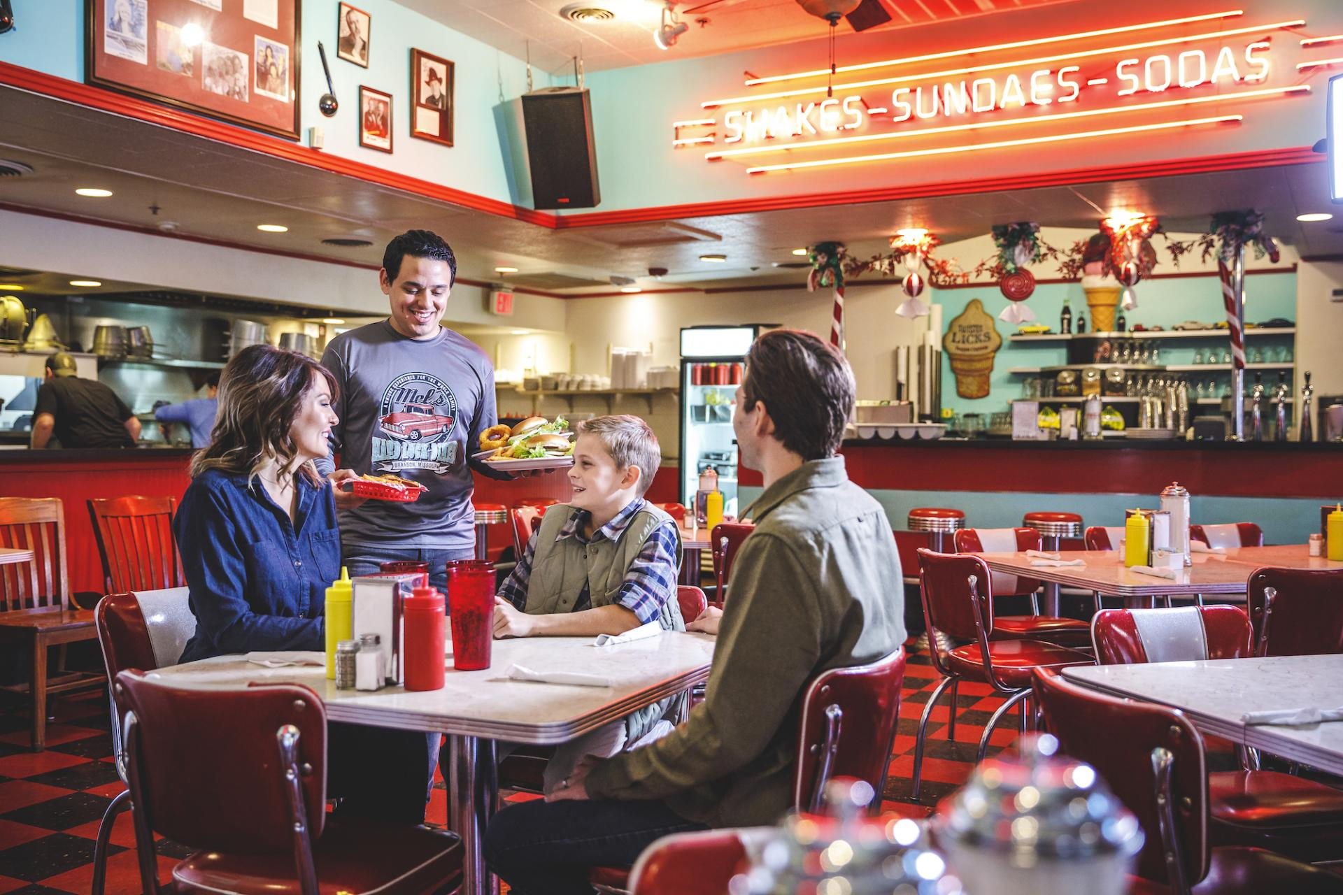 Family of three being served food at Mel's Hard Luck Diner in Branson.