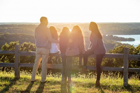Family sits on fence while enjoying sunset over rolling hills and a lake.