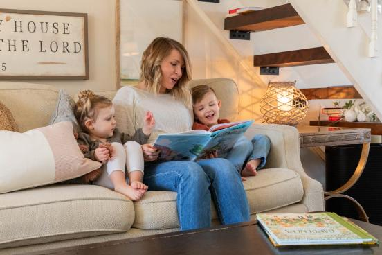 Woman reading a book to her two children inside their home in Branson.