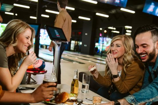 Group of friends eating and drinking at a bowling alley night club.