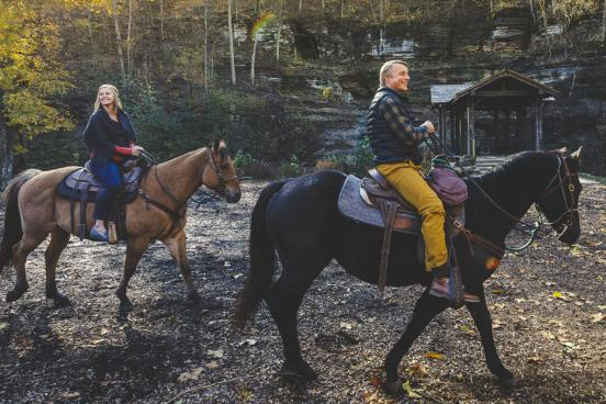 Husband and wife riding horses through a nature park in Branson in the fall.