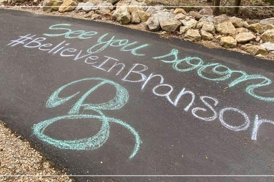 Chalk art of a Branson message on a local walking path.