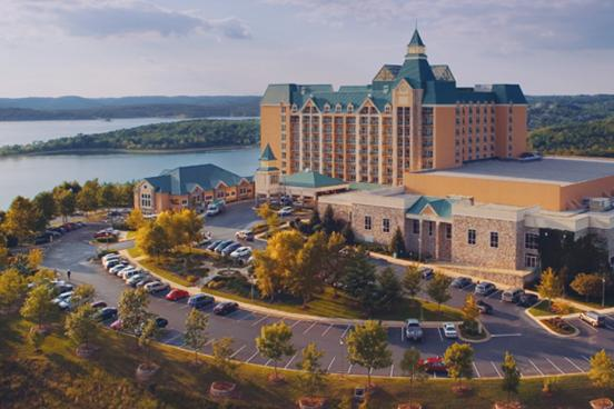 Large, multi-story resort hotel sitting on the shore of a large, scenic lake in Branson.