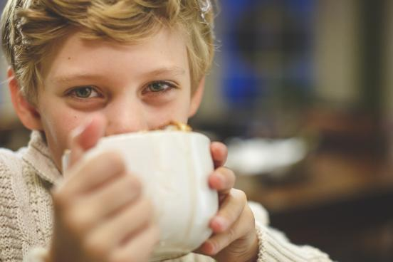 Young boy drinking hot chocolate.