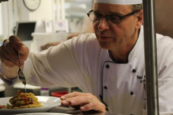 Executive chef decorating a plate of food to be served at the Keeter Center restaurant in Branson.