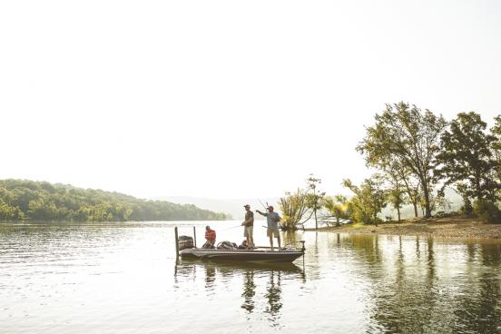 Three men fishing on fishing boat in the middle of scenic lake in Branson.