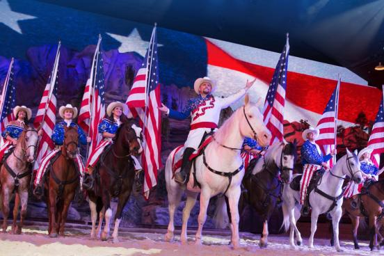 Large group of performers on horses holding American flags at dinner show attraction in Branson.