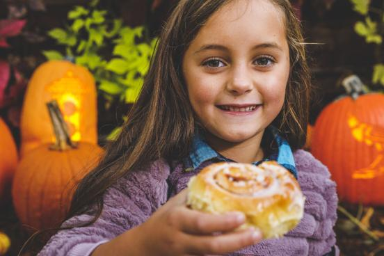 Young girl surrounded by pumpkins at a fall festival and eating a large cinnamon roll from a theme park in Branson.