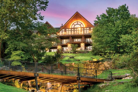 Front view of scenic log cabin hotel with waterfalls in the front lawn in the Ozark Mountains