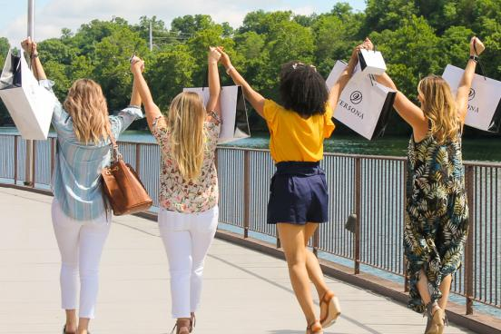 Four women holding hands and holding shopping bags at the Branson Landing for a girls' weekend getaway.