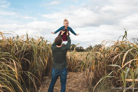 Dad holding daughter up in the air in the middle of a corn field.