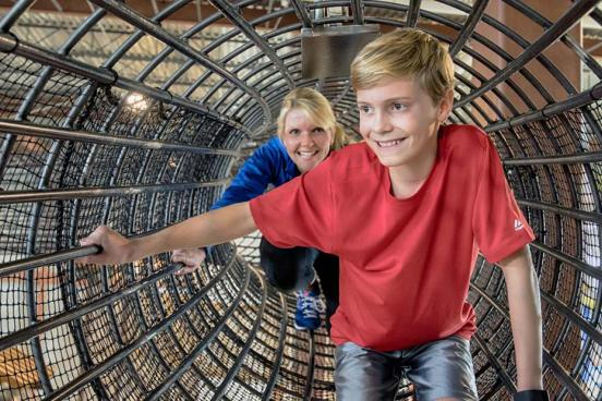 Mom and son adventuring in a rope tunnel at Fritz's Adventure