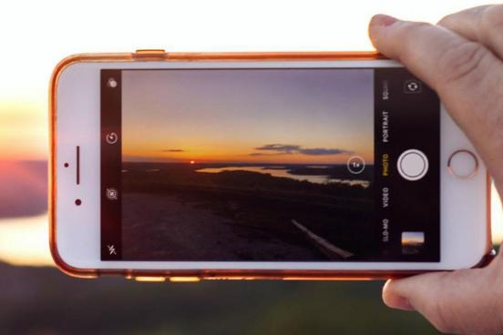 Hand holding a phone that is taking pictures of a scenic sunset and distant lake.