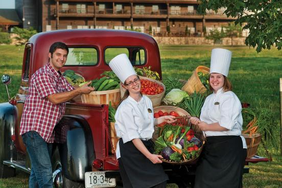 Three college students in the back of an old truck displaying fresh vegetables for a farmer's market in Branson.