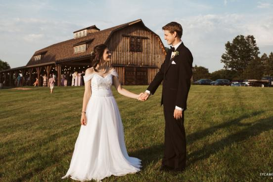 Recently marries couple holding hands in front of a barn wedding venue