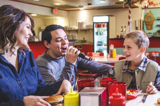 Mother and son being served food by a singing server at a restaurant in Branson.