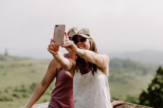 Two women surrounded by a beautiful nature scene are taking a selfie with their phone camera.