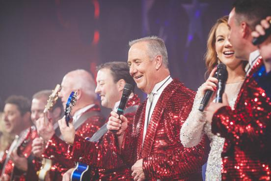 Line of live show music performers in red, white and blue costumes on a Branson stage.