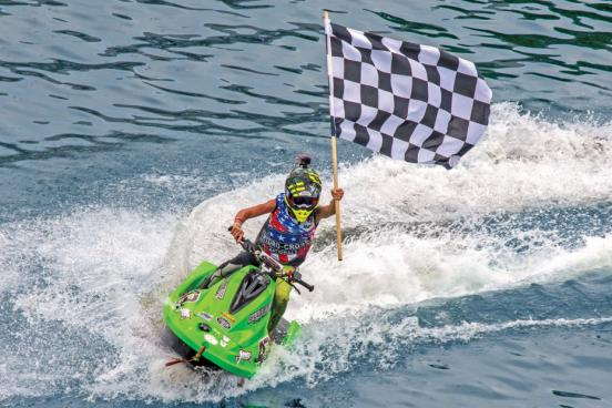 Powerboat driver holding flag during race in Branson.
