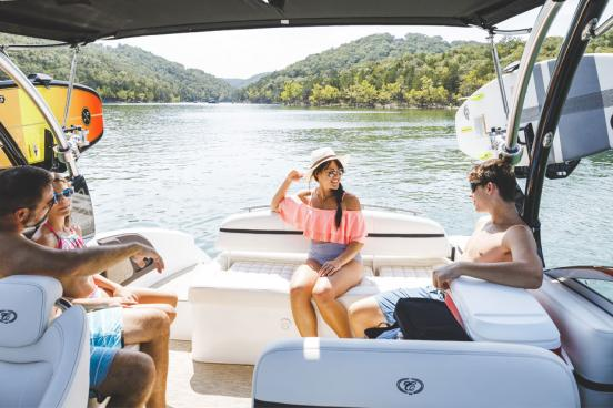Family of four sitting on the back of a boat during summer, enjoying the Ozark Mountain scenery on a lake in Branson.