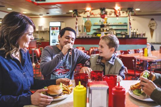 Dad, mom and son being served classic American burgers, fries and milkshakes by a singing server in Branson.