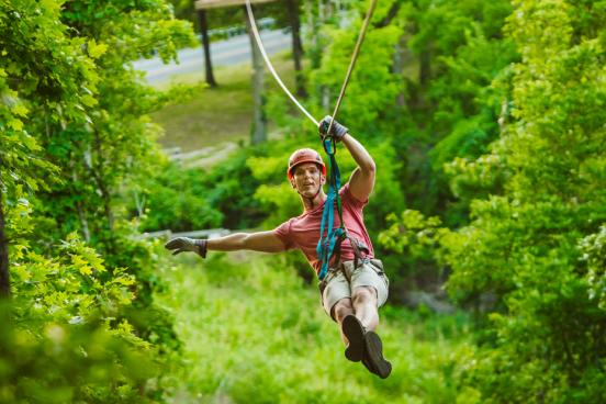 Man traveling on zipline through a forest of trees in Branson.