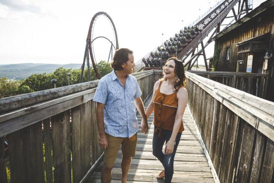Couple holding hands and walking in front of a roller coaster ride at Silver Dollar City theme park in Branson.